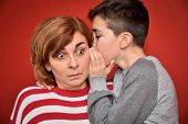 Young boy whispering secret into ears of surprised mother poster