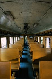 Kanchanaburi, Thailand - December 10, 2013: Inside old Thai diesel train with a few passengers sitting down