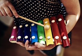 Close-up of kid playing on xylophone. Child development concept.