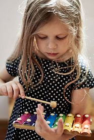 Cute blond child playing with xylophone at home. Creativity and education concept.