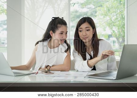 Young Happy Friends Working In Office. Two Beautiful Asian Woman Sitting In Office With Laptop And D