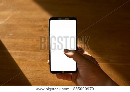 Holding A Smartphone With Empty Screen In A Hand, On A Background Of Wooden Table With Sunlight