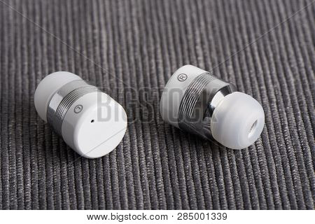 Close-up Of Wireless Cordless Bluetooth Stereo Earbuds On A Fabric Background