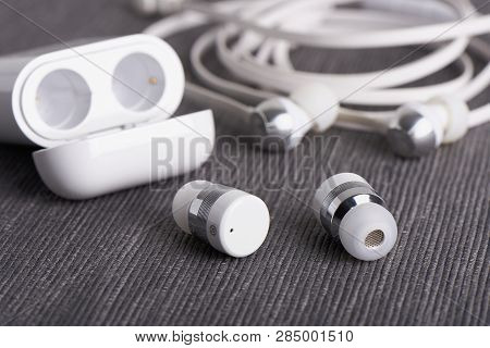 Wireless Cordless Bluetooth Earbuds With Chargeable Case On A Background Of Cable Earphone