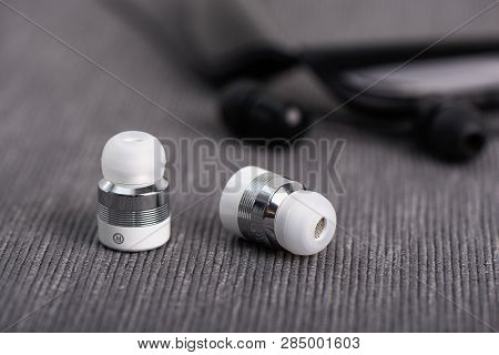 Wireless Cordless Bluetooth Earbuds On A Background Of Neck Band Type Earphone