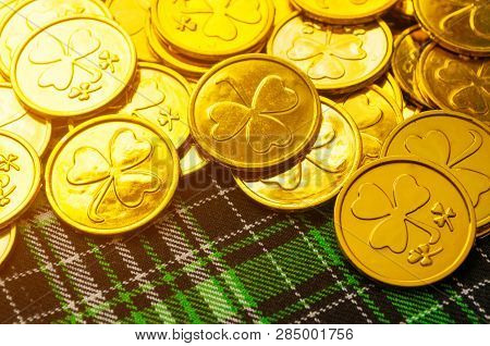 St Patrick's Day background. Golden coins with shamrock on the green checkered texture cloth under soft sunshine, St Patrick's day concept. St Patricks day festive card. Festive St Patricks Day background