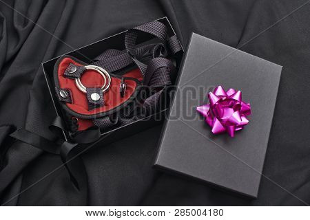 Ideal Bdsm Gift. Close up photo of a gift box with bdsm stuff laying on a black silk poster