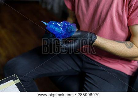 Tattoo Artist Doing Tattoo In Tatoo Salon. Master Makes Tattoo In Tattoo Studio