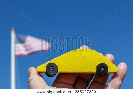 Yellow wooden car holding against blue sky with american flag