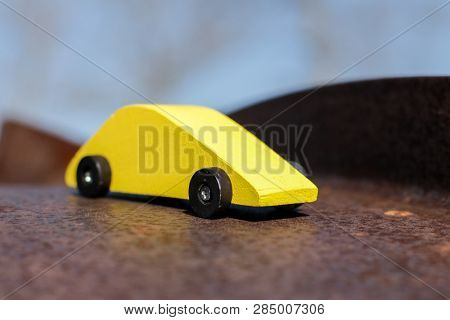 Yellow wooden toy car on metal road