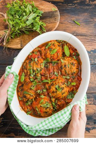 Fish Rissoles  In Spicy Tomato Sauce With Fresh Mint. White Dish On Wooden Rustic Table, Woman Hands