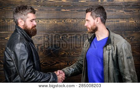 Brutal Bearded Men Wear Leather Jackets Shaking Hands. Friendship Of Brutal Guys. Approved Business
