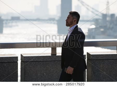 London, Uk - 19 April, 2018: Young Businessman  Walking Over The London Bridge On The Way To Work In