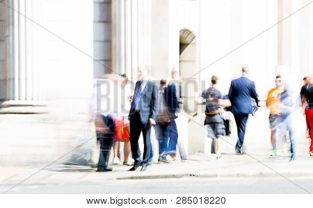 Motion Blur Of Walking People. Modern Competitive Life Concept. People Walking Next To The Bank Of E