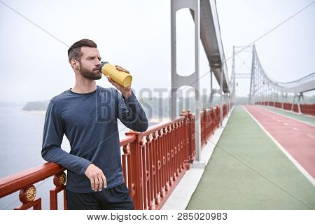 Tired After Jogging. Young Manin Sports Clothing Bending And Looking Tired While Standing On The Bri