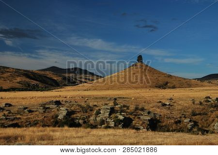 One Tree Hill With With Yellow Grass And Other Hills Around During A Summer Day Near Otago Central R