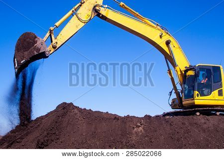A Large Construction Excavator Of Yellow Color On The Construction Site In A Quarry For Quarrying. D