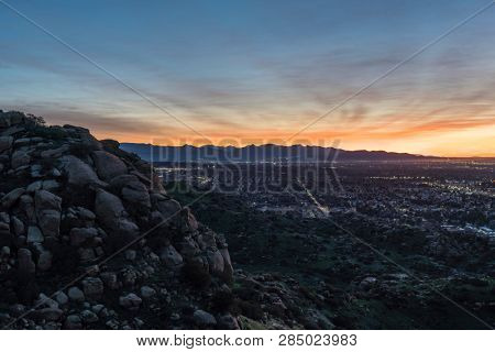 Dramatic dawn view of the San Fernando Valley neighborhoods from rocky hilltop in the city of Los Angeles, California.