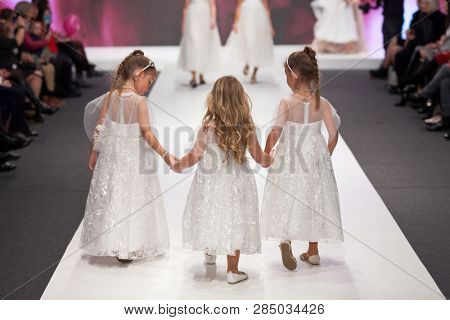 ZAGREB, CROATIA - FEBRUARY 02, 2019: Three girls in bridesmaid's dresses walking down the runway at the Wedding fair