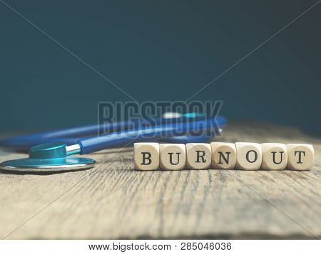 The Word Burnout On Small Wooden Blocks With A Stethoscope On A Wooden Table, Medical Or Health Care