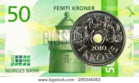 1 Norwegian Krone Coin Against 50 New Norwegian Krone Banknote