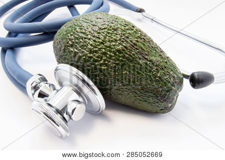 Green Avocado Raw Fruit Lies Surrounded By Stethoscope, Which Analyse It. Facts And Benefits Of Avoc