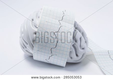 Concept Of Brain Exam As Ecg Waves. Shape Of Human Brain Entwined With Paper Tape Elektrokardiogramm
