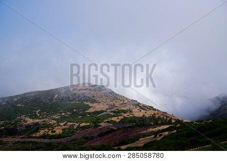 Mountain Road Against Dense Clouds On Pico Do Arieiro. Portuguese Island Of Madeira