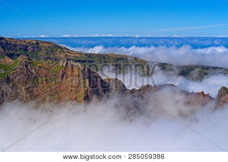 Mountain Peaks In The Clouds Against Clear Blue Sky. View From Pico Do Arieiro On Portuguese Island
