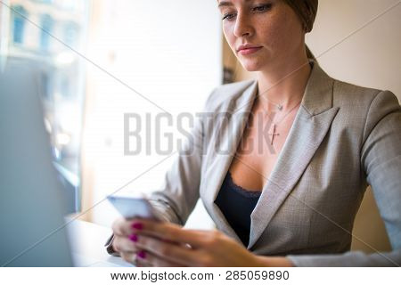 Woman Secretary Using Apps On Cell Telephone While Sitting With Notebook Device In Office Space. Fem