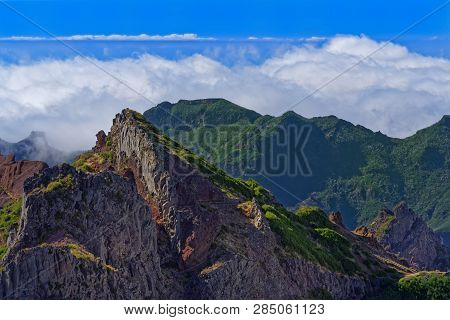 Panoramic View Of Mountain Peaks Against Clouds Below Horizon And Clear Blue Sky On Sunny Day. View
