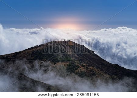 Amazing Scene Of Mountain Peak And Dense Clouds Against Sky And Orange Colored Sunlight. View From P