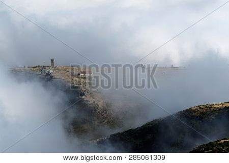 Looking Through The Clouds At An Abandoned Building On The Mountain Peak. Scenic View From Pico Do A