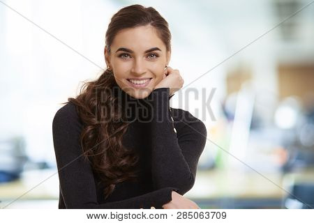 Beautiful Smiling Young Woman Standing In The Office And Looking At Camera