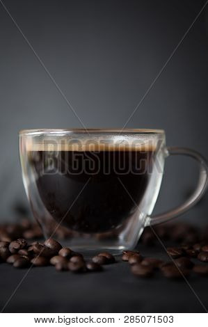 Coffee Cup With Fresh Brewed Coffee And Brown Roasted Coffee Beans Scattered On Dark Stone Backgroun