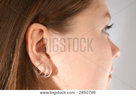 Close-up of multiple ear piercings on young girl. poster