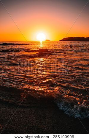 Orange Teal Sunset On A Beautiful Beach. Beautiful Vivid Sunset Over Beach With The Water Vivid. A B