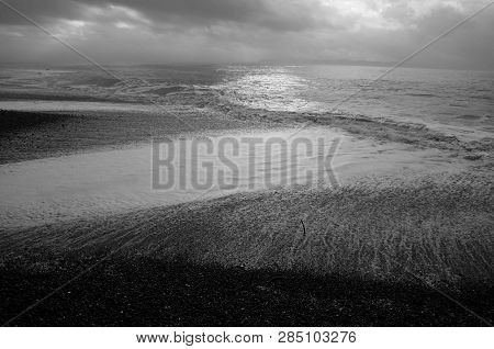 Sunlight Glints Off Of Foaming Waves As They Crash Against The Beach, Mountains Obscured By Fog In T
