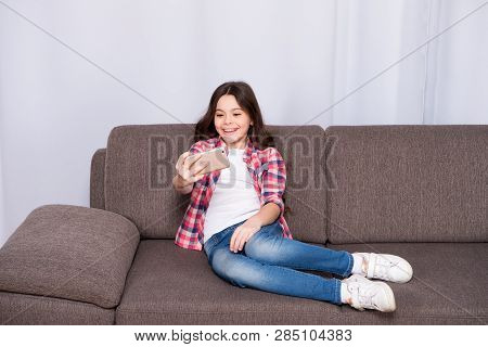 Video Call Concept. Child Relaxing On Couch And Communicate Online. Girl Hold Smartphone Taking Self