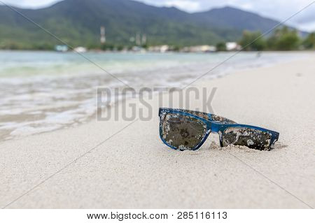 Old Sunglasses Overgrown With Algae And Shells, On The White Sand Of A Tropical Beach
