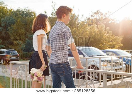 Teen Youth Couple Boy And Girl Standing Back, Summer Sunny Day, Girl Holding Bouquet Of Flowers In H