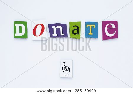 Word Donate From Cut Letters On White Background. Donation Concept. A Word Writing Text Showing Dona