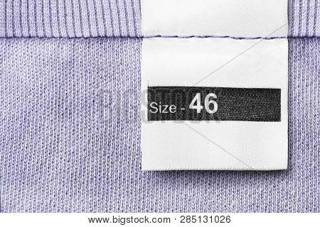 Size 46 Clothes Label On Violet Textile Background Closeup