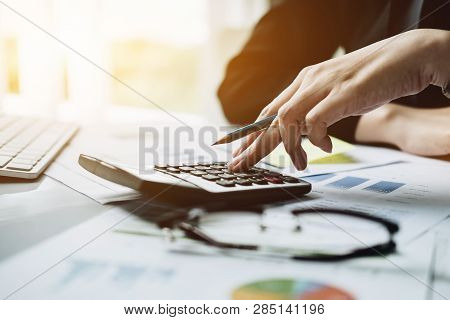 Accountant With Calculator Counting Making Notes At Office Hand Is Writes In A Postit Sticky