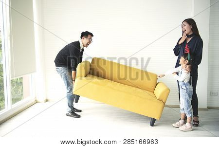 Asian Family Moving Sofa In Living Room At New Home Together.