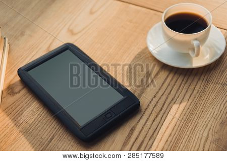 Ebook With Blank Screen Lying Near Cup With Coffee