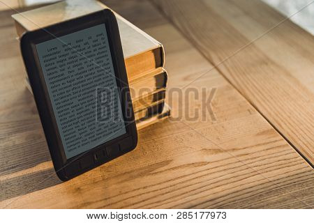 Black Ebook Near Paper Books On Wooden Table