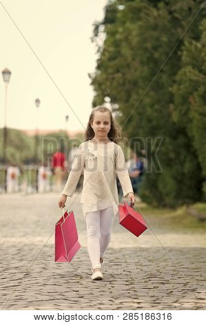 Girl Shopping On Calm Face Carries Shopping Bags, Urban Background. Kid Girl With Long Hair Fond Of