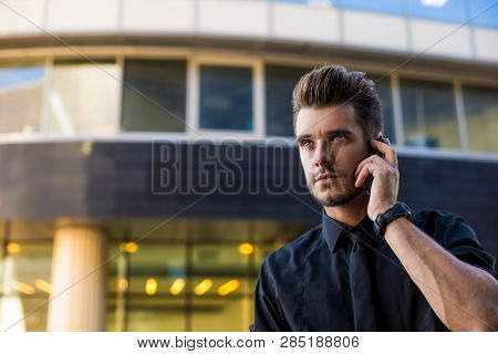 Handsome Man Skilled Lawyer Talking With Client Via Mobile Phone While Standing Outdoors Against Bus