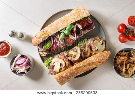 Variety Of Beef Baguette Sandwiches With Champignon Mushrooms, Green Salad, Fried Onion, Tomatoes Se